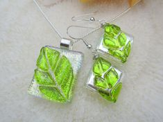 These beautiful dichroic glass Leaf Earrings are made of silver dichroic glass between 2 layers of clear glass to make it glossy and shiny and to give it depth. Transparent green leaf is tack fused on the base. The earrings are wrapped in Argentum silver wire, which connects it to the hook.  This listing is only for the earrings, the pendant on the first picture is available over here: https://www.etsy.com/listing/187248650  COLOR: silver, green SIZE (without bail): 11/16 x 11/16 or 1.4 cm x…