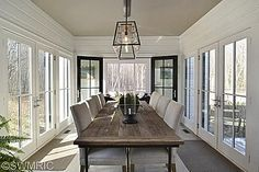 Dining room meets sunroom. Gray Parsons chairs, simple, bright, industrial light fixture, black framed doors