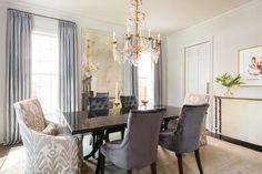 Love It or List It - French dining room features a glossy black lacquered dining table lined with purple velvet tufted dining chairs as well as gray ikat dining chairs placed at each end of the table illuminated by a French crystal chandelier placed in front of an antiqued French floor mirror flanked by windows dressed in blue silk drapes.