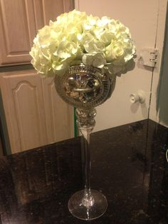 Simple DIY wedding decor!  Tall mercury glass vase (Homegoods $8), add water, apply 4 strips of tape to the top of the vase opening to create a 9 square grid, prep your flowers, and arrange!  I used two hydrangeas and about 10 garden roses to adorn the top ($13)! This picture was taken after the arrangement sat overnight! Doable the day before :)