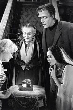 The Munsters of 1313 Mockingbird Lane in the city of Mockingbird Heights. Marilyn (Pat Priest), Grandpa (Al Lewis), Herman (Fred Gwynne), and Lily (Yvonne De Carlo).