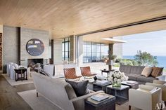 In this Malibu home designed by Scott Mitchell, armchairs by Kuriger and vintage Ross Littell woven-leather lounge chairs flank a group of ceramic tables by Michael Smolcich; a work by KAWS hangs above the fireplace, and the carpets are by Mansour Modern.