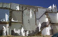 Foto de una fachada de una casa destruida. Se ve las paredes internas. Varios personajes han sido dibujado encima de la foto, como si esta g...