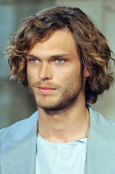 Mid length, curly hairstyle for men. Love the beachy waves with no frizz. The subtle golden highlights look great, too.