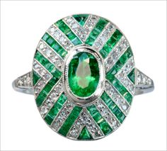 1920-30s Art Deco Emerald and Diamond Ring. Features a .55ct oval emerald surrounded by step-cut emeralds and diamonds, set in a chevron style pattern.