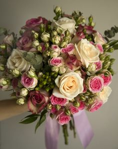 Rustic pink bridal bouquet with spray roses and green berries