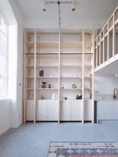 East End apartment, UK, by EBBA Architects. A double-height storage wall made from white-stained pine emphasises the ceiling height of the main living space in this London apartment.