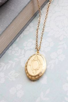 This a beautiful matte gold locket with etched vintage inspired details. A beautifully romantic locket necklace that has two frames inside for your photos, mementos and keepsakes. This is an oval matter gold plated brass locket with a satin Hamilton gold plated brass chain. This necklace has a high quality lobster clasp closure. Locket measurement - 29mmx22mm approx. (1 1/8 x 7/8) The chain length can be between 18 - 28 and you can select you preferred length at checkout. Charms: If you…