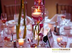 Wedding reception table setting and centerpiece with floating candle and pink flowers. www.kevintrimmer.com