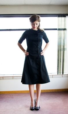 Lincoln Square from Shabby Apple  French coat detailing combines with structured black sateen.  Black offset buttons run from the knee-length hem to the left collar bone, creating a dynamic line.  Black dress