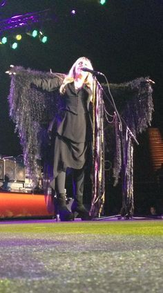 "Stevie Nicks live performance on stage:  Rock and Roll Goddess Stevie Nicks of Fleetwood Mac stretches out her arms while wearing her ""NAY-TIV RAY-VIN: EnFold"" raven wings inspired shawl by CricketsKnits.  2015 Image by fan Stephanie Dubick"