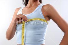 Slim woman measuring breast