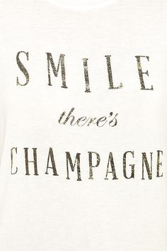"""A glass of bubbly and the Daydreamer Smile There's Champagne Cream Tee are always a recipe for happiness! Soft and lightweight jersey knit tee has a crew neckline, short sleeves, and subtle high-low hem. """"Smile There's Champagne"""" is spelled out on front in gold-flecked letters."""