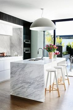 white #kitchen - space is anchored by the black walls and the copper accents add a warm natural beauty