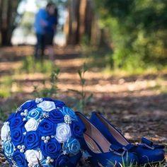 """Buquê de flores cetim em azul royal , azul claro e branco com broches prateados, pérolas e strass. <br> <br>Os buquês são personalizados e montados de acordo com o gosto da noiva. <br> <br>Eles são únicos sendo que nunca existirá um buque idêntico ao outro. <br>Composto de broches em tons de prata cravejados em strass, flores de cetim e pérolas. <br> <br>Possui 19cm diâmetro <br> <br>A escolha do buquê de noiva é tão importante quanto a escolha do vestido. <br>O """"Bouquet de Broches"""" é uma…"""