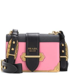 Prada - Cahier leather shoulder bag - Opt for an instant icon with Prada's Cahier leather shoulder bag. This charming piece is inspired by the bindings of antique books and features aged gold-tone hardware to further the vintage vibe. Compact in size and with a thick shoulder strap, this is an easy-carry companion with endless appeal. The use of colour block leather brings statement appeal – we love the sweet pink hue in contrast to the classic black trims. seen @ www.mytheresa.com