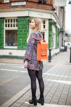 Our Sales Supervisor Maya wears our Portrait Backpack in Ember Orange.