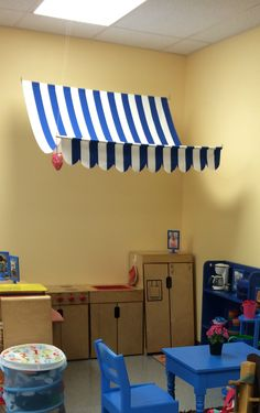 I searched everywhere on Pinterest for an easy awning design that would differentiate the dramatic play area from the rest of the classroom. I ended up designing this myself. I switch it out with every theme. Just two yards of fabric, two dowel rods, hooks & eyes and fishing line. It's easy to switch out!