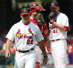 St. Louis Cardinals manager Mike Matheny returns to the dugout after conferring with starting pitcher John Lackey (background right) and cat...