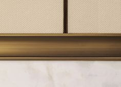 Modern panelling sits against the classic marble, separated by inlayed bronze trim that also acts as a handle detail