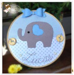 Quadro Porta Maternidade (Bastidor) <br> <br>Modelo - Elefantinho Azul <br> <br>Confeccionado em tecido e feltro, decorado com botões, pérolas e personalizado com o nome do bebê. <br> <br>Tamanho - 30 cm de diâmetro <br> <br>Podemos fazer com qualquer tema, cor e estampa, consulte-nos. <br> <br>Rendas, fitas e laços - poderão variar de acordo com a disponibilidade no fornecedor, antes de efetuar a compra nos contate. <br> <br>Produto exclusivo ATELIER BELLY: cópia-não-autorizada. <br…