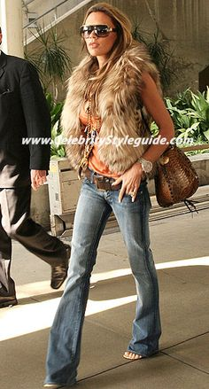 Victoria Beckham in bootcut jeans and faux fur vest.