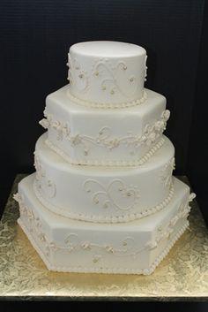 Wedding Cake:Off white wedding cake with hexagonal tiers and off white designs. www.sugarhillsbakery.com
