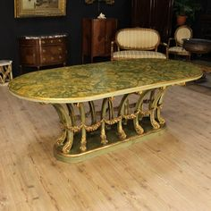 Pric: 3200€ Italian table of the 20th century. Furniture in carved, lacquered and gilded wood. Table with wooden lacquered faux marble top. Furniture of good stand stability decorated with 14 lacquered and gilded legs joined to each other by golden garlands. In good condition, with some little drops of lacquer. #antiques #antiquariato Visit our website www.parino.it