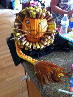 Lion no carve pumpkin. 2nd grade class Pumpkin for school contest. Glued thumb tacks onto bottom of corks, let kids paint them and stick on pumpkin. Used yellow, gold and brown paint. Braided yellow yarn tail with orange ribbon weaved in. Glued on feathers on end of tail. Gold pipe cleaners for whiskers. Green colored wiggly eyes. So easy and it turned out GREAT!!!!