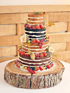 A pretty autumnal naked wedding cake delivered to Cripps Barn in the Cotswolds. A 4 tier with sticky toffee, lemon, chocolate and vanilla tiers decorated with fresh fruits and currants with some pretty leaves and flowers too.