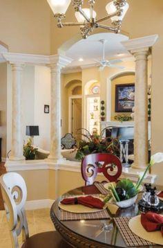 Open floor plan, tuscan-style dining room. #diningroom #chandelier #columns #housetrends