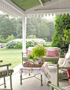 The view from this front porch takes in hydrangea bushes and the woods beyond.