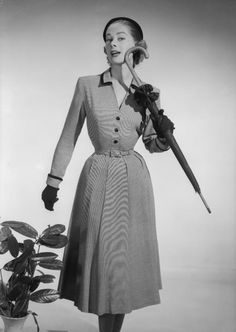 Brilkie Fashion, April 26, 1954: A woman modelling a Brilkie dress with gloves and an umbrella. (Photo by Chaloner Woods/Getty Images) #1950s