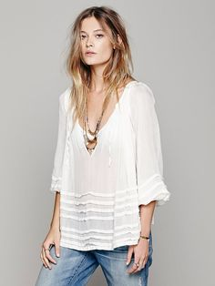 Free People FP ONE Tie That Binds Blouse, Sheer blouse in a delicate weave, featuring a deep pleated V-Neckline, gathered wrists, and a shapeless silhouette. Pintuck pleats form a horizontal stripe pattern on the lower bodice and sleeves. Tie across neck.