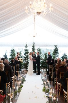 Tented wedding ceremony with evergreen trees, chandelier, and candles | Winter wedding at Stein Eriksen Lodge in Deer Valley, Utah. Black tie wedding, under a soft fabric tent, with glowing candles, gold Chivari chairs, lush white flowers, evergreens trees and branches, and black accents | Planning: Soiree Productions | Flowers: Decoration Inc. | Photography: Melissa Kelsey Photography | http://www.melissakelseyphotography.com