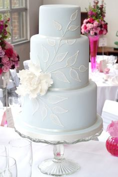Pale blue wedding cake with leaf and flower detailing