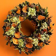 """Quince and Hydrangea Wreath - $69.00   Dried quince slices, naturally green hydrangea, and purple oregano are artfully arrayed with flax pods and painted eucalyptus. Display wreath indoors or in a protected outdoor area.  4""""D. x 16""""dia."""