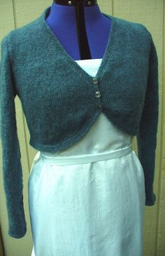 """The Slate Blue Knit Bolero Shrug is the perfect cover-up for the bride at her wedding reception. The Bolero is made of an Angora Blend Yarn, it is soft and warm, but lightweight. It can go from casual to formal, but you will feel luxurious no matter what. Size Large fits up to 42.5"""" bust 23.5"""" long sleeves 3 button closure 40% Angora, 60% Acrylic yarn You should wash by hand in cold water with soap for delicates. Air dry flat. Do not dry clean. Other colors and sizes are available, just m..."""