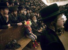 A child dressed as a clown participates with other ultra-Orthodox Jewish men in the Purim festival at a synagogue in Jerusalem, March 8. The Jewish holiday of Purim celebrates the Jews' salvation from genocide in ancient Persia, as recounted in the Scroll of Esther.