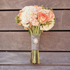 Though these aren't the particular flowers I would choose, I love the combo of white green and peach, and also love the relatively modest size and shape of this bouquet.