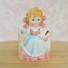 Little Miss Muffet sat on a tuffet eating her curds and whey. Along came a spider, who sat down beside her and frightened Miss Muffet away! This vintage planter is sweet and convenient. Made of ceramic with a paint glaze, it features Miss Muffet, her bowl and spoon and the spider to