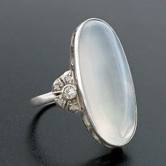 A moonstone and diamond ring from the Art Deco (c 1920) era. The ring is made of platinum and portrays a large oval shaped cabochon moonstone with diamond accents. The moonstone is bezel set within a mounting that displays a lovely wirework setting.