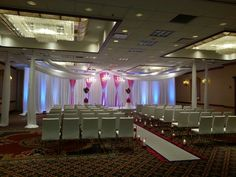 White leather versa chairs, designed backdrop,  rented chandaliers,  led lighting, ceiling drape