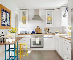 White kitchens will never go out of style. You're more likely to grow tired of bold hues on major surfaces, so stick with accessories you can swap out to get that kiss of color. Consider your kitchen's stone floor, backsplash, and trim to find the perfect shade of white for the space. /