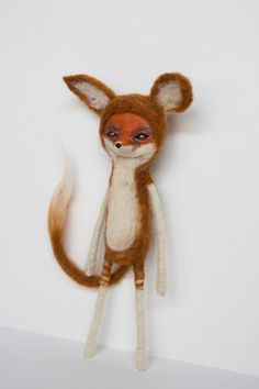 This ooak fox art doll was made with needle felted wool and clay. The face, which is clay, has been painted in acrylics and features eyes made of