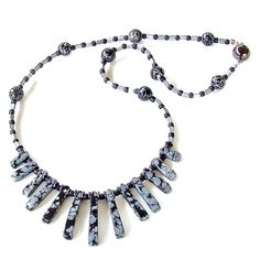 "Saturn's Lair: Black and Gray Gemstone Necklace This necklace of snowflake obsidian with metallic accents creates a modern Boho look. Closes at 18.5 "" with a magnetic clasp."