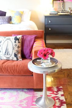 @Nikki Rappaport Home Tour // coffee table layout // orange couch // pink and orange // gray ikea console table // photo by Sarah Winchester Studios