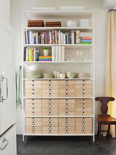 """""""A one-stop-shop bookshelf like this is helpful for a number of reasons: the top half is great for storing cookbooks, dishes, and serving ware, while the small cubby drawers on the bottom are perfect for flatware, utensils, linens, and other kitchen miscellanea."""""""