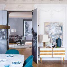 Des touches d'or dans la salle à manger de cet appartement de Saint Germain des Prés. Autour de la table en marbre, de jolies chaises turquoise et un petit buffet chiné.