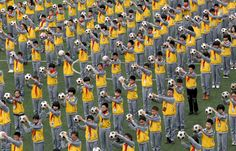 Students do morning exercises with footballs on a playground at a primary school in Linhai, Zhejiang province